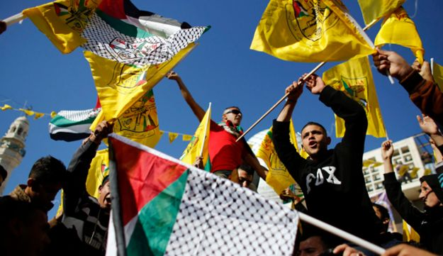 Fatah supporters wave flags during a rally marking the 48th anniversary of the founding of the Fatah