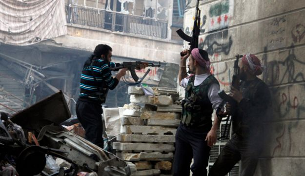 Free Syrian Army fighters fire at enemy positions during heavy clashes with government forces