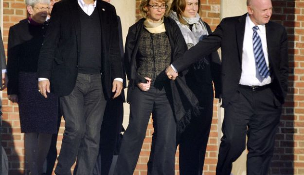Former U.S. Rep. Gabrielle Giffords, center, holds hands with her husband, Mark Kelly