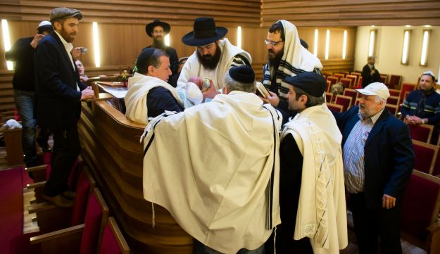 A mohel doctor is surround by other rabbis and relatives as he holds a boy at his circumcision.
