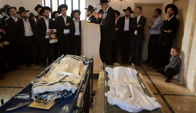 Ultra-Orthodox Jews stand around the remains of Jacob Giacomo and Therese Tedesco