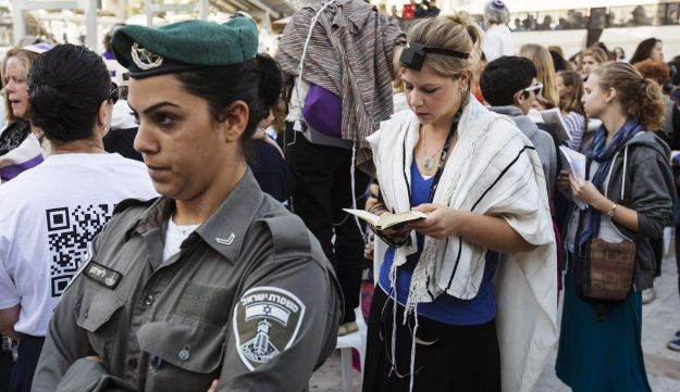 A female Israeli border police stands guard as a member of Women of the Wall, wearing a prayer shawl