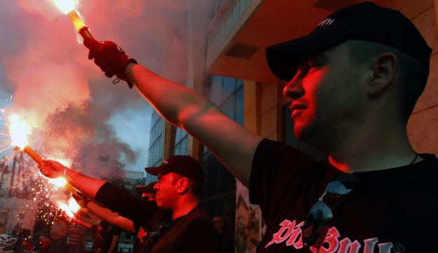 Members of the Greek extreme right Golden Dawn party hold red flares outside the town hall