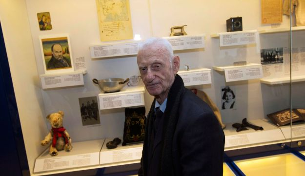 Shlomo Resnik, 83-year old Holocaust survivor, stands near a display featuring a bowl