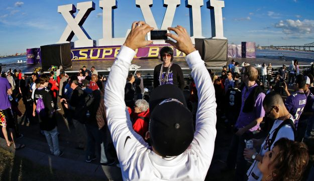 A fan takes a picture in front of the Super Bowl XLVII sculpture on a barge along the Riverwalk