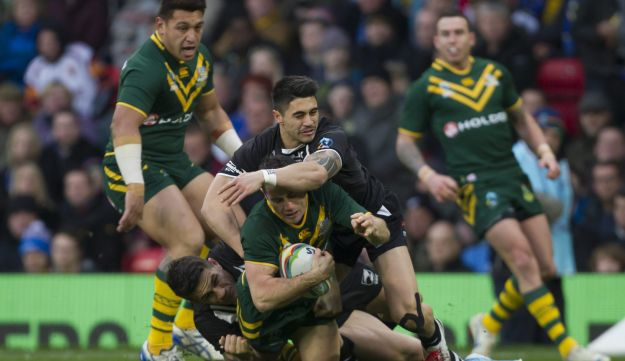 Australia's Cooper Cronk, with ball, is tackled by New Zealand's Sonny Bill Williams