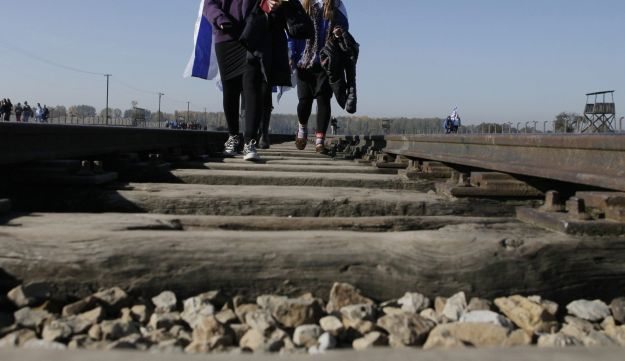 Visitors with Israeli flags walk on the historic tracks inside the grounds of Auschwitz