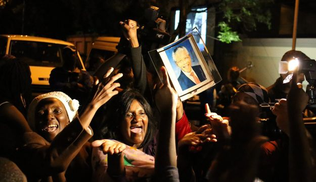 South Africans hold pictures of Nelson Mandela