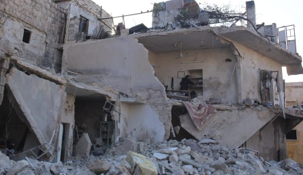 A woman inspects her damaged home in Aleppo December 15, 2013.