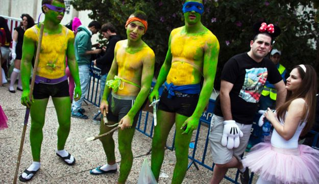 People in costumes, take part in a street party for the Jewish holiday of Purim in Tel Aviv