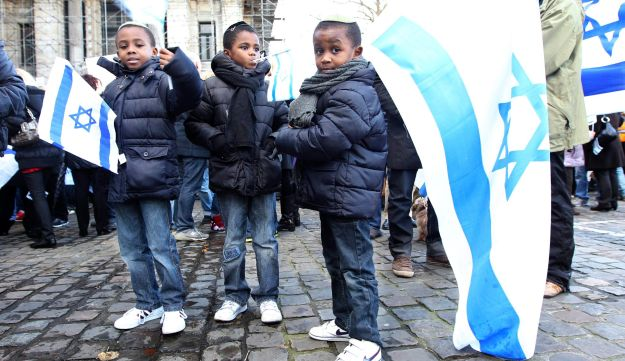 Boys with Israeli flags participate in a solidarity march for Israel in Brussels, Belgium