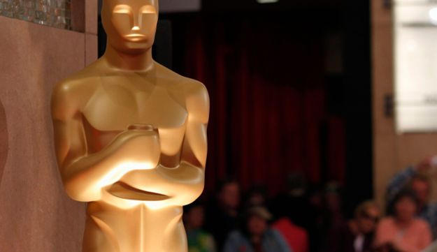 People look at an Oscar statue during preparations for the 85th Academy Awards