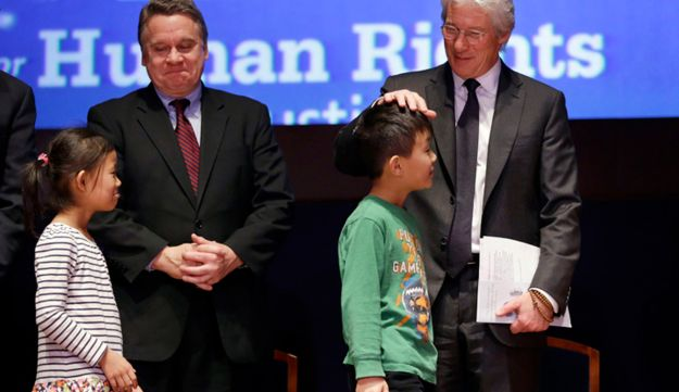 Rep. Chris Smith, R-N.J, left, standing by Chen Ke Si, 7, smiles