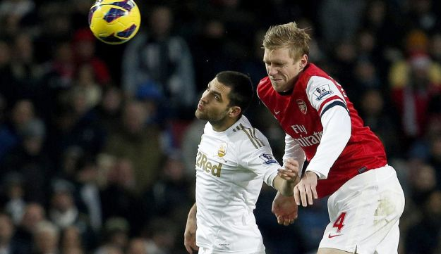 Arsenal's Per Mertesacker, right, vies for the ball in the air with Swansea City's Itay Shechter