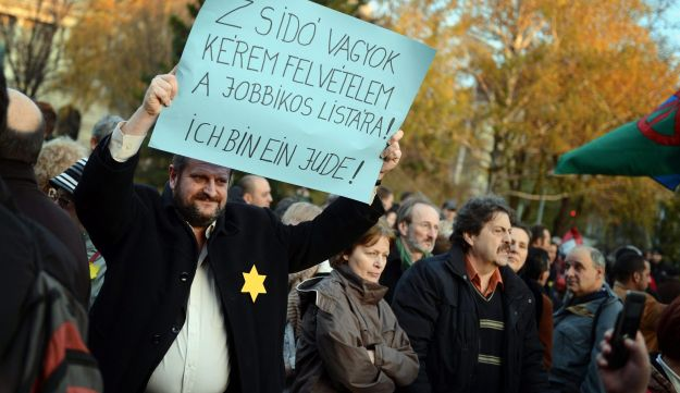 A demonstrator holds a placard that reads 'I am a Jew. Please, include my name on the Jobbik-list',