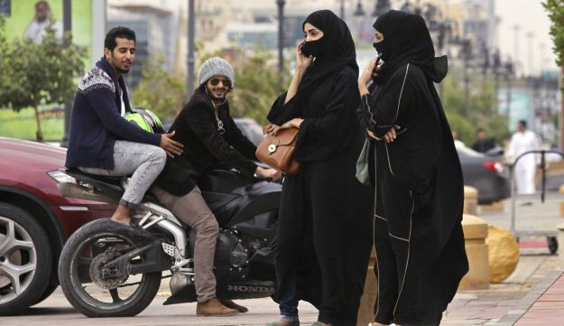 A woman speaks on the phone as men ride a motorcycle on a cloudy day in Riyadh, Nov. 17, 2013.