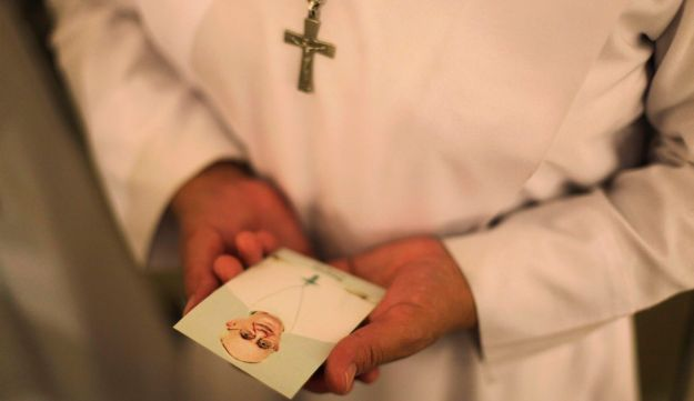A nun holds a photograph of Pope Francis during a Thanksgiving Mass for the newly elected pope