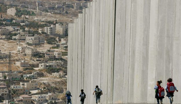 File photo: Palestinian school children walk past a section of the separation barrier in Abu Dis.
