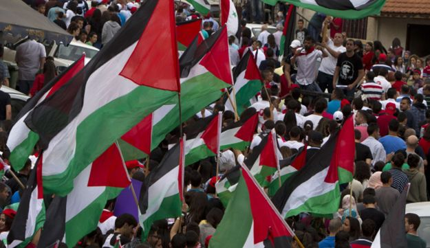 Israeli Arabs wave Palestinian flags during a rally in the northern Arab-Israeli town of Sakhnin