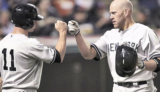 Kevin Youkilis, right, bumps fists with Brett Gardner.