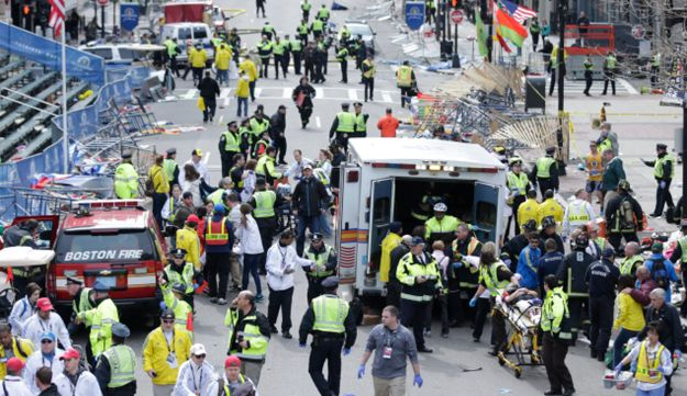 Medical workers aid injured people at the finish line of the 2013 Boston Marathon