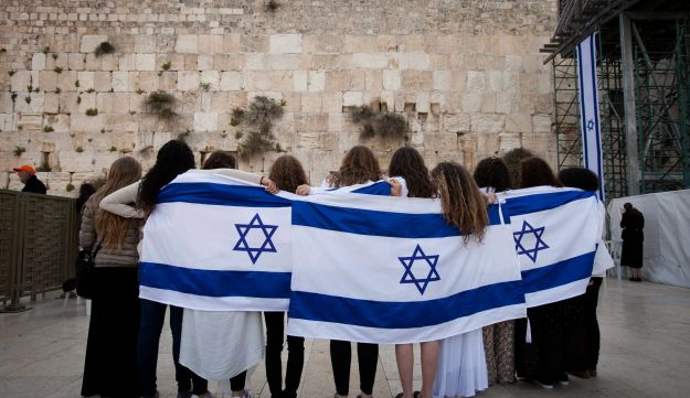 Young women wrap themselves in Israeli flags at the Western Wall