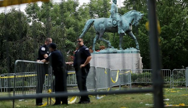 Police stand watch near the statue of Confederate Gen. Robert E. Lee in Emancipation Park the day after a white nationalist rally devolved into violence, Charlottesville, Virginia, August 13, 2017.