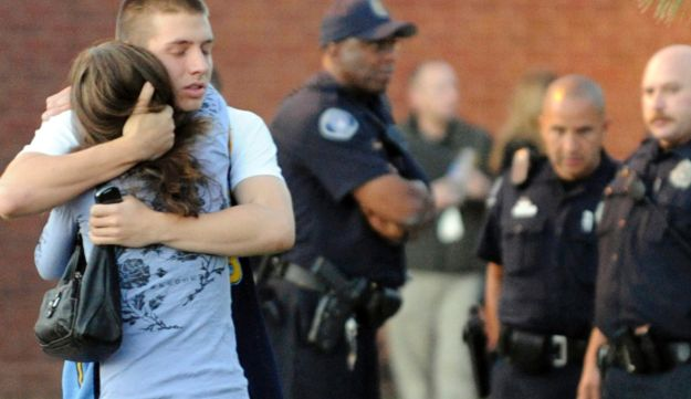 Eyewitness Jacob Stevens, 18, hugs his mother Tammi Stevens after being interview by police.