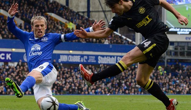 Everton's Phil Neville (L) challenges Wigan Athletic's Jordi Gomez during their English FA Cup socce