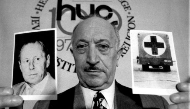 Simon Wiesenthal displays two pictures, which he says refer to Nazi criminal Walter Rauff, May 1973