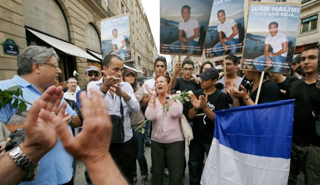 Demonstrators carry photographs of Ilan Halimi , roses and French flag after the verdict of the tria