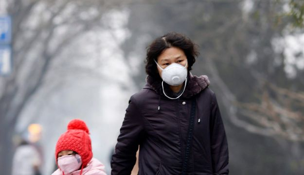 Woman and a girl wearing masks make their way amid the heavy haze in Beijing.