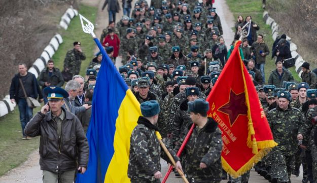 Ukrainian servicemen carry flags.