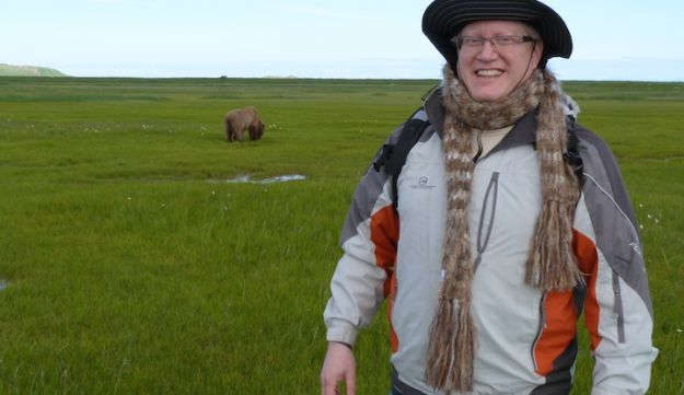 Donn Ungar posing in Alaska with a grizzly bear in the background.