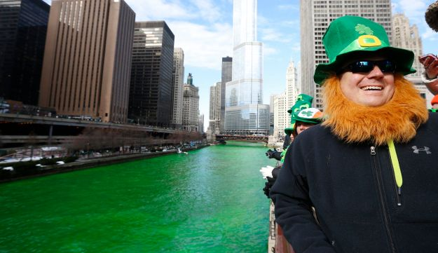 A man dressed as a leprechaun stands beside the dyed green Chicago River.