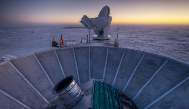 The sun sets behind the BICEP2 telescope, foreground, and the South Pole Telescope in Antarctica