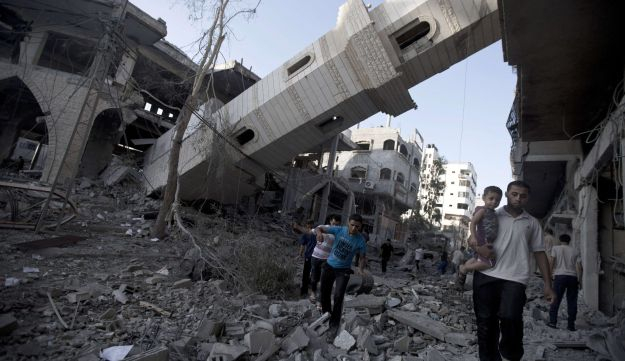 Palestinians walk past the collapsed minaret of a destroyed mosque in Gaza City. July 30, 2014