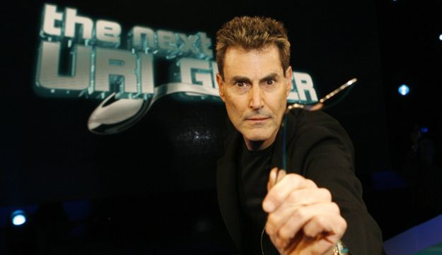 Uri Geller poses with a spoon which he bent for photographers in Cologne January 6,