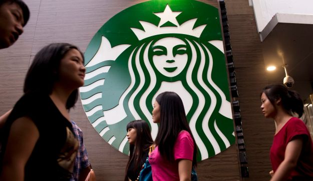 Pedestrians walk past a Starbucks Corp. store in the Luohu district of Shenzhen, China