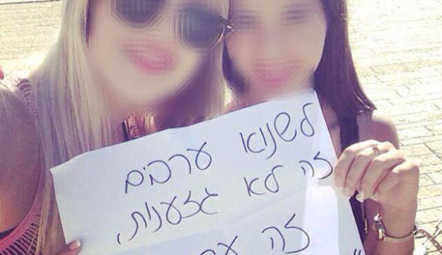 Two girls hold a sign that reads, 'Hating Arabs isn't racism, it's values.