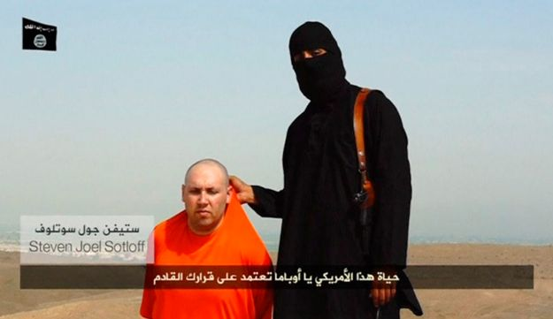 A masked Islamic State militant speaks next to a man purported to be U.S. journalist Steven Sotloff