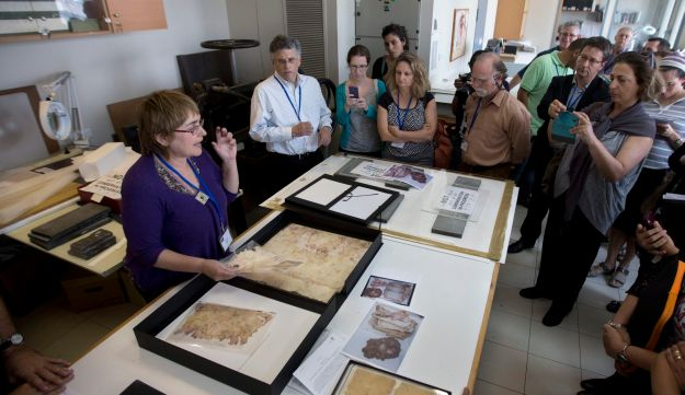 A worker shows restored documents at the Yad Vashem Holocaust memorial paper conservation laboratory