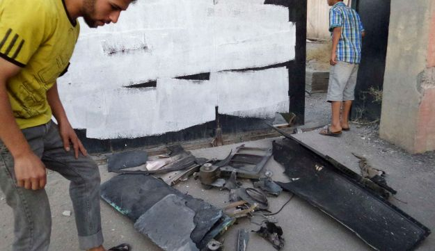 A man inspects the remains of what Islamist State militants say was a U.S. drone which crashed into