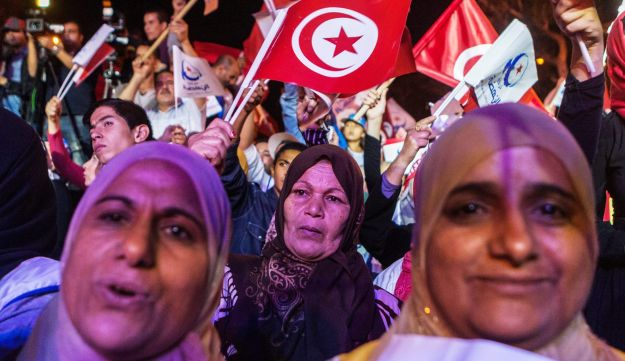 Supporters of the moderate Islamist Ennahda Party wave party flags during a campaign rally in Tunis, October 25, 2014.