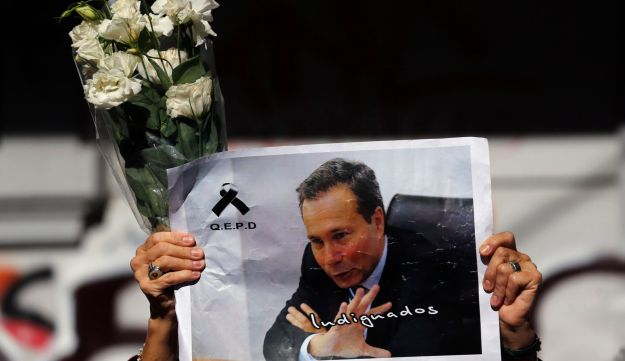 A woman holds up flowers and an image of late prosecutor Alberto Nisman