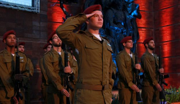 Israeli soldiers stand at attention before the start of the Holocaust Remembrance Day ceremony
