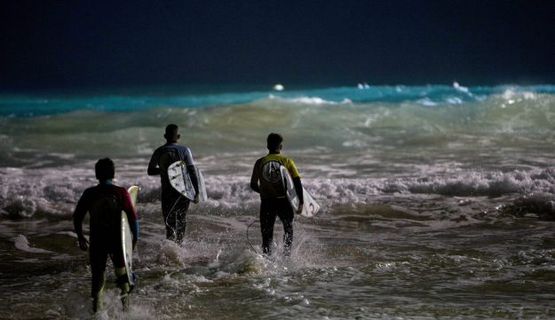 Israeli surfers enter the water to surf during a night surfing competition in the Mediterranean Sea