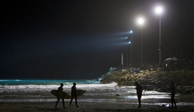 Israeli surfers wait to surf during a night surfing competition in the Mediterranean Sea in Ashdod