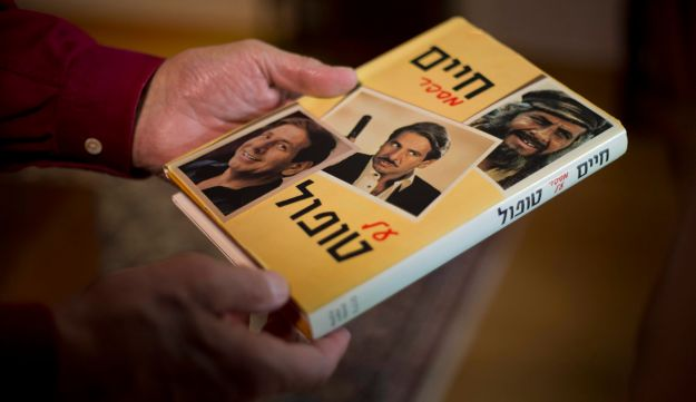 Chaim Topol holds a book about his career, during an interview, in Tel Aviv, Israel, April 8, 2015.