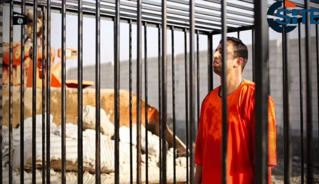 Jordanian pilot Lt. Muath al-Kaseasbeh standing in a cage just before being burned to death